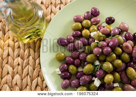 Close-up of marinated olives with olive oil on bamboo mat