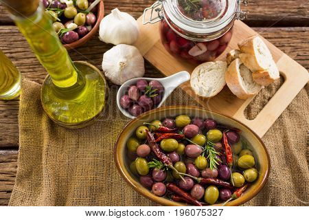 Marinated olives with ingredient and breakfast on wooden table