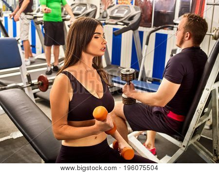 Woman holding dumbbell workout at gym. Girl with bare belly. Friends men with heavy dumbbells on background. Barbell in background number one. Female loves to train with dumbbells.