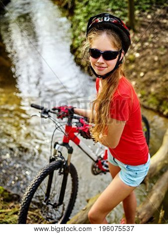 Bicycle teen with ladies bikes in summer park. Womens road bike for running on nature. Girl cycling fording throught water. Cycling trip is good for health. Girl is traveling alone. poster