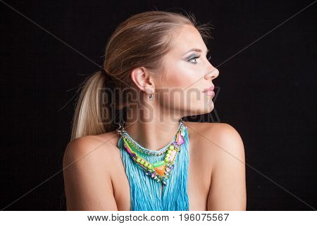 beautiful young blonde  woman beauty portrait profile ponytail with attractive large blue necklace with fringe studio shot