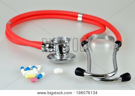 Close up of rd stethoscope and pills