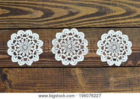 Top view of lace doily on wooden background
