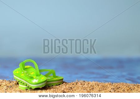 Close up of flip flops on the sandy beach