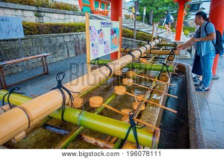 KYOTO JAPAN - NOVEMBER 24, 2016: Unidentified people washin their hands at hand wash pavilion in Fushimi Inari Shrine in Kyoto, Japan.