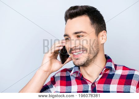 Excited Young Handsome Brunet Guy Is Talking On His Smart Phone And Smiling. He Is Wearing Checkered