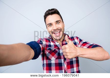 Successful Excited Young Guy In Casual Wear Is Making Selfie Shot On Camera, Standing On A Pure Back