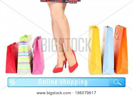 Young woman in high heel shoes with paper bags and text ONLINE SHOPPING in search bar of internet browser on color background