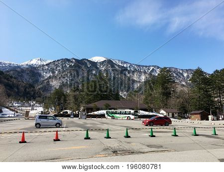 KAMIKOCHI JAPAN - APRIL 20 2017: Parking for public transport in the National Park of Kamikochi on the background of the mountains