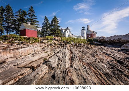 Pemaquid Point Lighthouse atop dramatic rocky coast in Bristol, Maine, on a beautiful summer day