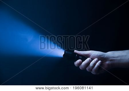 The flashlight in the man's hand from the right side of the frame in black and blue color isolated on black background