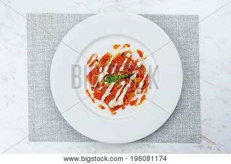 Ravioli with tomato sauce served in white plate on marble serface.
