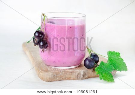 Cocktail of yogurt with black currant berries in a glass on a wooden board. The cocktail is decorated with bunches with black currant berries. Side view