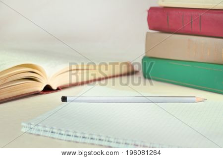 Multicolored book stacked up and an open book next to a notebook for notes. The concept of education knowledge and self-development