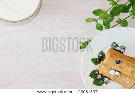 pancakes with currants and mint dusted with powdered sugar and sour cream in bowl on wooden background