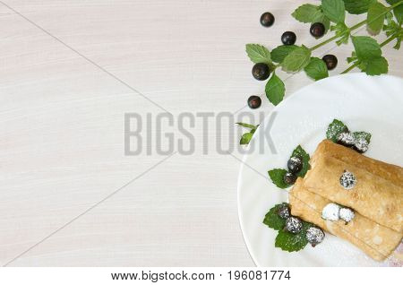 pancakes with currants and mint dusted with powdered sugar in bowl on wooden background