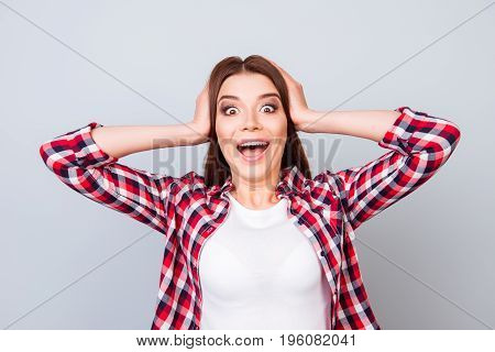 Cute Amazed Brunette Girl In Shirt, Holding Her Head, She Is Shocked, Extremely Happy, With Wide Ope