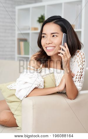 Cheerful Vietnamese woman sitting on sofa and talking on phone