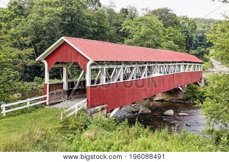 The historic red Barronvale Covered Bridge crosses Laurel Hill Creek in rural Somerset County Pennsylvania.