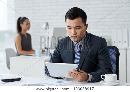 Serious businessman reading information on tablet computer