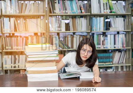 Young Girl Student with Glasses Reading book Overlap Serious Hard Exam Quiz Test Sleeping headache worry in Classroom Education Library University Knowledge center