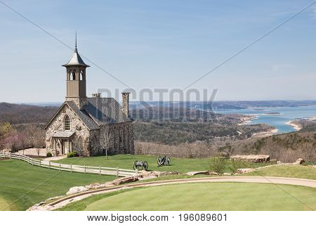 absolute  beautiful quaint little stone and brick church sitting on manicured green lawn with rolling hills and a big lake in the background.