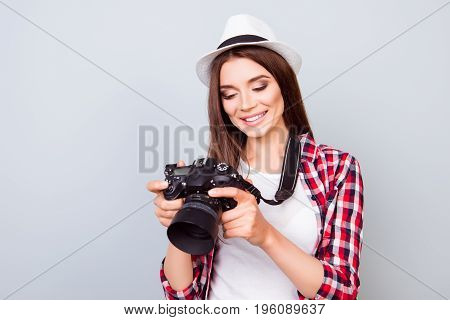 Young Attractive Brunette Photographer Is Smiling On The Blue Background. She Is Excited And Holding