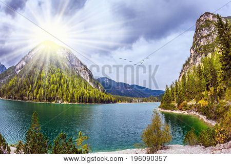 Sunshine on autumn day. Magnificent lake in South Tyrol, Italy. The concept of environmental and hiking. Water reflects the surrounding mountains and forest