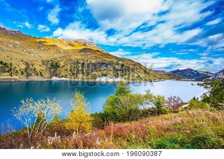 Glacial lake with clear cold water. The concept of ecological tourism. The harmony of the Dolomites. Mountain Lake Lago di Fedaia