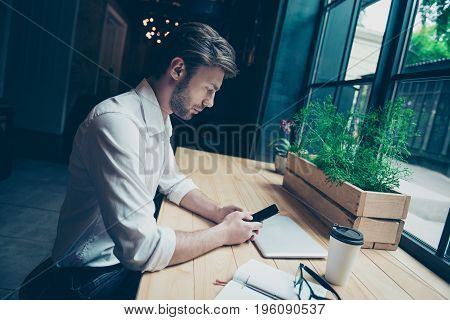 Time For A Break. Young Student Is Sitting In A Dark Modern Restaurant, Texting On His Phone, Well D