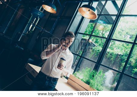 Successful Young Man, Stands Near Window With View On The Garden, Has A Business Conversation,  At W