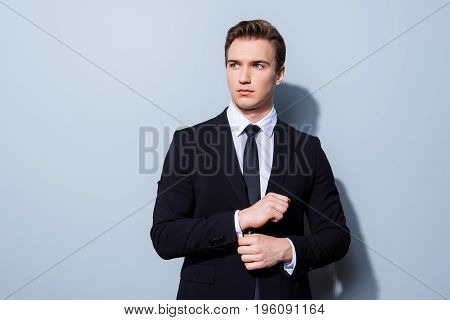 Young Handsome Businessman Banker In A Suit Is Fixing His Cuff Links, He Stands On Pure Light Backgr