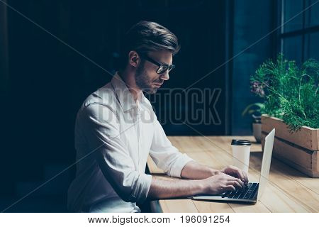 Side Profile Photo Of A Ponder Young Man In Formal Wear, Sitting At His Work Place In A Loft Styled