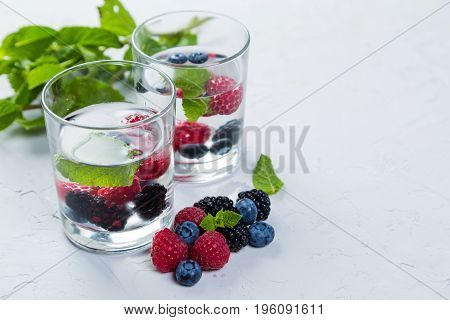 Infused water with berries and mint, rustic background