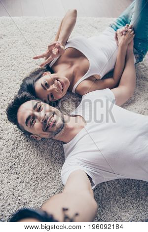 Cheerful playful ltino mulatto sister and brother are taking selfie and making funny grimaces gesturing. They lie on the floor on beige carpet in white casual outfits indoors at home