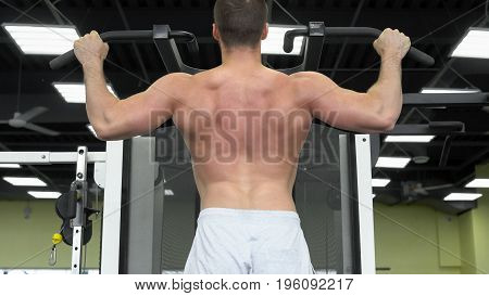 Young Muscular Man Trains At The Gym. Athlete Of Weight Training