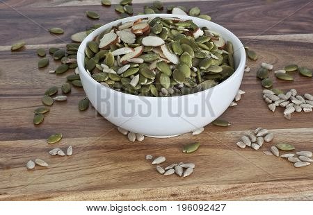 pumpkin and sunflower seeds in a white bowl on the table