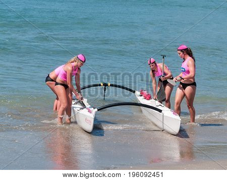 Mount Maunganui, New Zealand - January 28, 2012;  Four women in pink tops returning to beach from surf with outrigger canoe in paddling competions at Mount Maunganui Surf Lifesaving 2012.