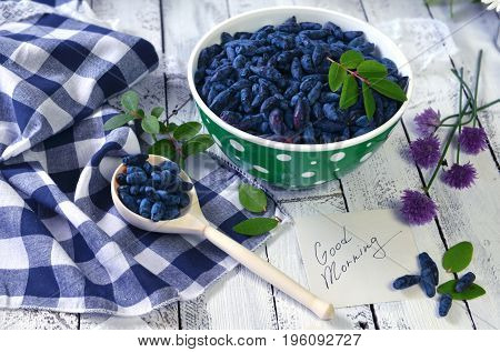 Note with good morning text, spoon and bowl full of ripe berries. Beautiful summer vintage background, vegetarian and vegan concept, rural still life with berry and flowers