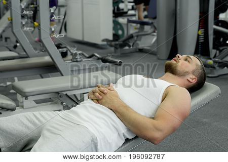 Muscular Tired Man Lies On A Bench After Exercise In The Gym