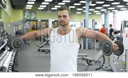 Portrait Of Strong Athletic Man At The Gym Training. Bodybuilder Does An Exercise For Shoulders With