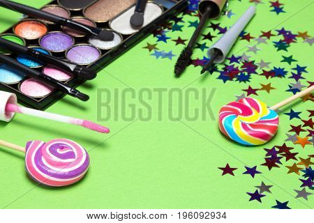 Holiday youth party makeup products with brushes, lollipops and confetti. Selective focus, copy space