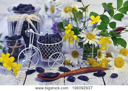 Vintage objects, spoon with honeysuckle berry and yellow flowers on the table. Beautiful summer vintage background, vegetarian and vegan concept, rural still life with berry and flowers