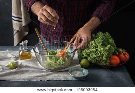 Man cooking vegetables salad in home kitchen. Male hands pouring lemon juice into salad