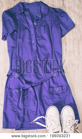 Sport chic fashion style. Blue dress and white sneakers on shabby wooden surface. Toned image