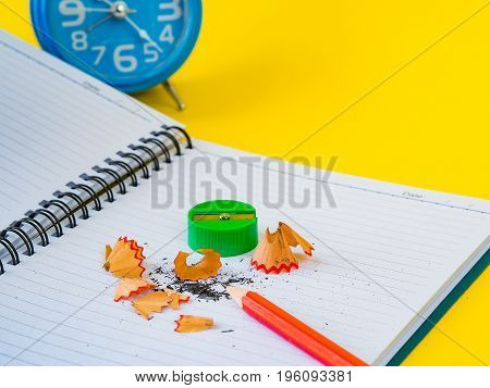 Office accessories including note book red pencil alarm clock and green sharpener on yellow background. Education and business concept.