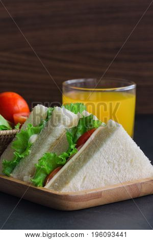 Triangle slice piece of sandwich ham cheese with lettuce and tomato on wood plate. Homemade sandwich served with orange juice for breakfast or lunch. Delicious ham cheese sandwich ready to served on granite table.Sandwich ham cheese spread.