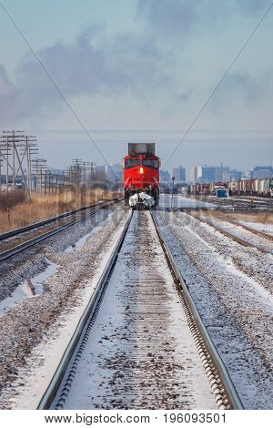 Head On View of Distant Red Train With Prairie City Skyline