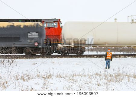 A crew member watches a passing train looking for issues