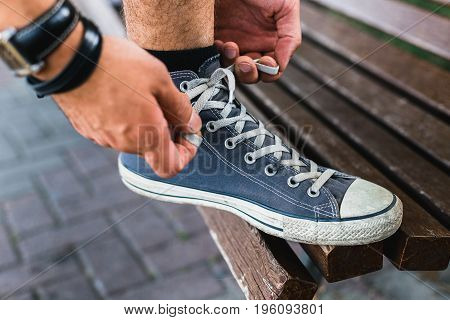 Hands Of Young Man Tying His Shoelaces Closeup. Lifestyle Activity Footwear Concept